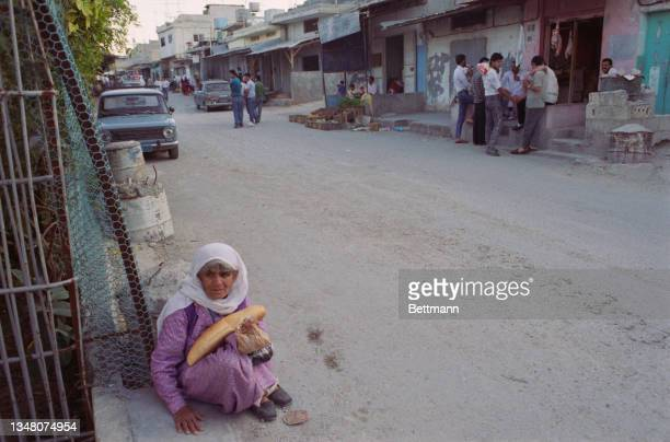 An elderly Middle Eastern woman sits on the ground, holding bread a brown paper bag in her arms, with two groups of men standing before buildings in...