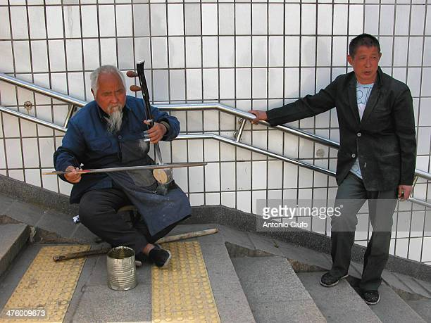 An elderly musician earn coins by playing in an underpass. Beijing is a city of great contradictions: poverty coexists with the exclusive and...