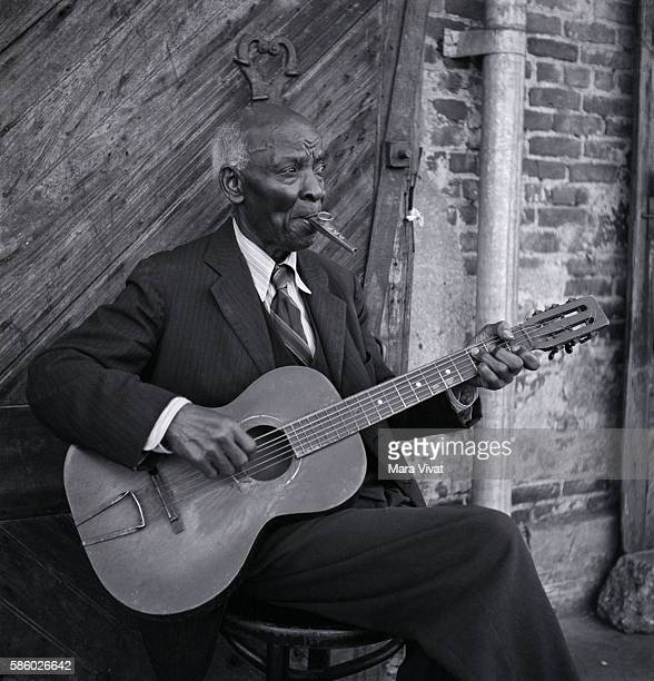 An elderly musician plays the guitar and kazoo simultaneously.