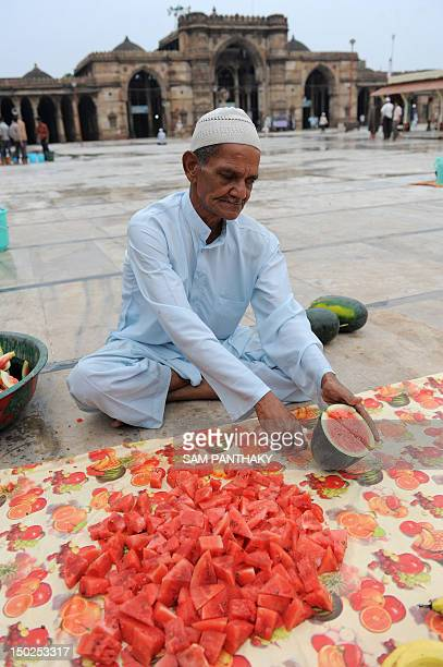 An elderly Muslim cuts fruit as he prepares to end the day's fast during Ramadan at the 600 year old Shahi Jama Masjid in Ahmedabad on August 13 2012...