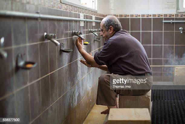 An elderly Muslim during the ritual ablution before prayer in the Shishan mosque on April 08 2016 in Sweileh Jordan