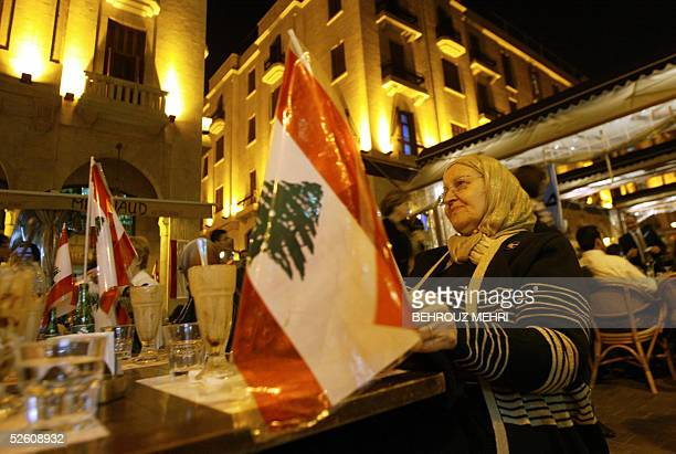 An elderly Muslim Lebanese woman is surrounded by national flags as she sits in an openair cafe in downtown Beirut 09 April 2005 as the Lebanese...