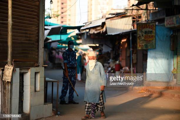 An elderly Muslim man walks past a ParaMilitary personnel from the Rapid Action Force wearing a facemask during a governmentimposed nationwide...