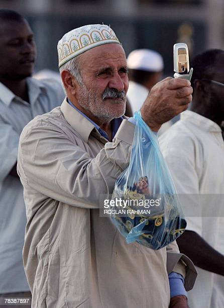 An elderly Muslim pilgrim takes a photograph of the Prophet Mohammed Mosque with his mobile phone in the holy city of Medina 11 December 2007 in...