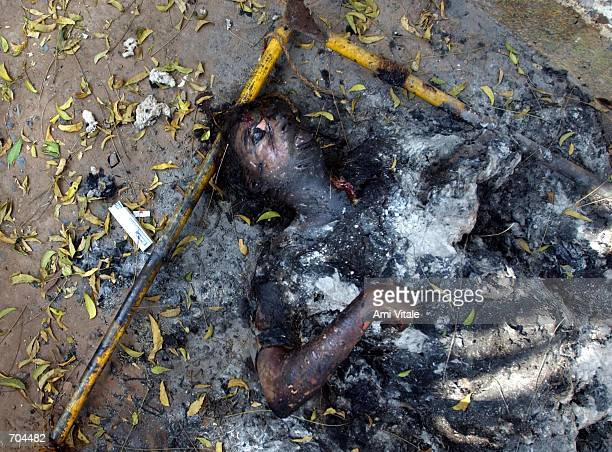 An elderly Muslim womans body, whose face and throat was slashed and then set on fire, lies outside of her home March 2, 2002 in Ahmadabad, India....