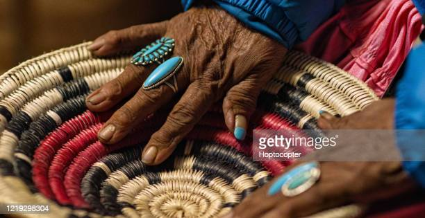 an elderly native american woman (navajo) wearing turquoise rings on her fingers touches a woven navajo basket - tradition stock pictures, royalty-free photos & images