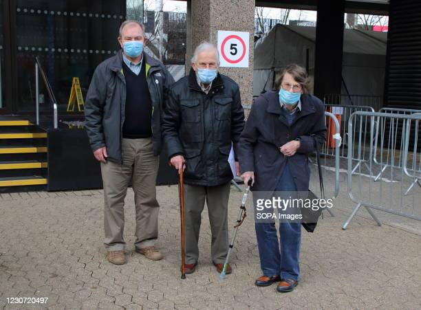 An elderly nurse with both her husband and son wearing face masks leave the vaccination centre after receiving their first dose of the Astra Zeneca...