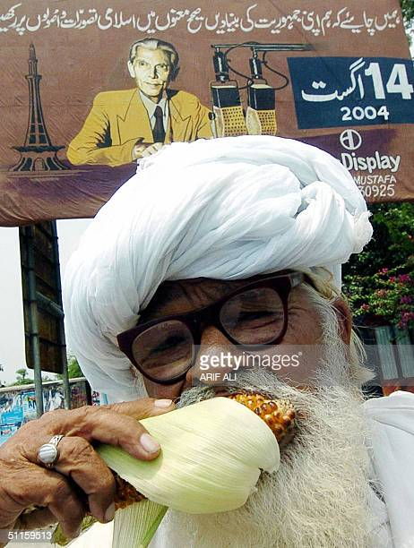 An elderly Pakistani man bites into a corn cob on a street where a billboard shows a protrait of country's first president Mohammad Ali Jinnah in...