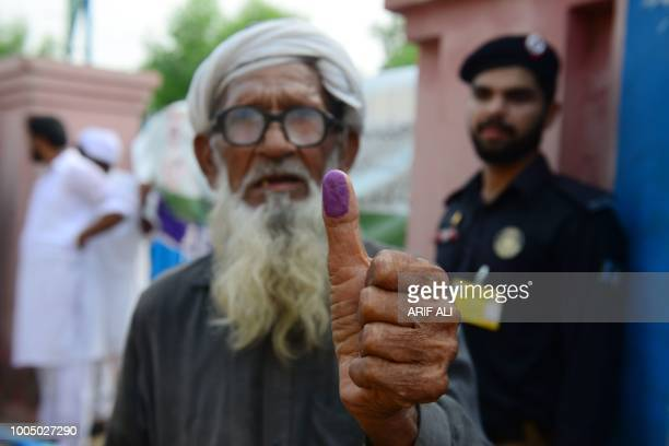 TOPSHOT An elderly Pakistani man shows his inked thump after casting his vote outside a polling station during general election in Lahore on July 25...