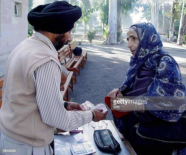 An elderly Pakistani woman exchanges money with an officialat the RBI counter prior to returning to Pakistan at the Wagah Border Post 04 January 2003...