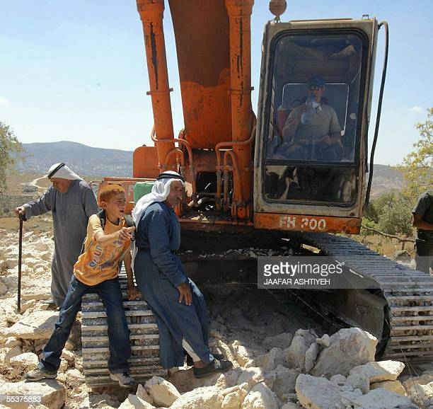An elderly Palestinian and his grandson sit on standing still bulldozer as Israeli soldiers scuffle with Palestinians and foreign activists...