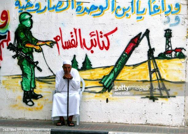 An elderly Palestinian man sits in front of a wall with a mural showing a masked militant from Ezz El-Deen Al-Qassam Martyrs' Brigade, the military...