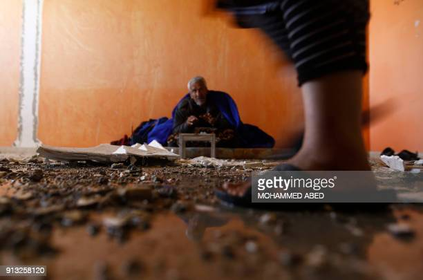 TOPSHOT An elderly Palestinian man sits inside his apartment which was damaged after an attack carried out by the Israeli army in Beit Hanun in the...