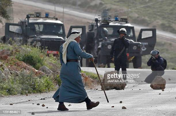 An elderly Palestinian man walks amidst clashes between demonstrators and Israeli security forces in the village of Beita, south of Nablus, after...