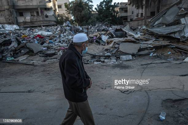 An elderly Palestinian man walks beside the rubble of a house, which was destroyed during an Israeli raid in the central Gaza Strip on May 18, 2021...
