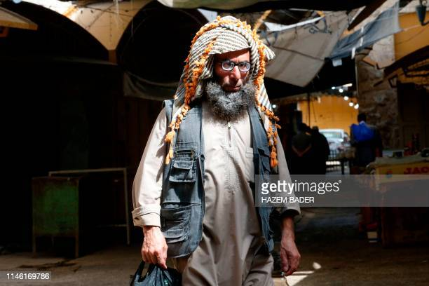 An elderly Palestinian man walks in the Palestinian side of the old city market in the divided West Bank city of Hebron during the Muslim holy...