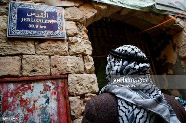 An elderly Palestinian man walks past a street sign indicating the distance to Jerusalem on December 5 in Hebron in the Israelioccupied West Bank /...