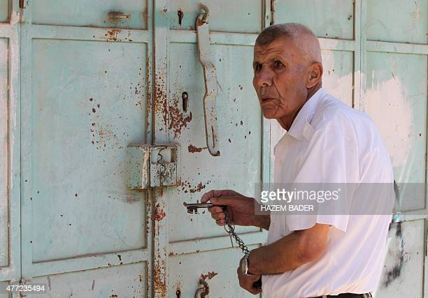 An elderly Palestinian storekeeper prepares to open his shop following a decision by the Israeli army to allow the reopening as of next Friday of...