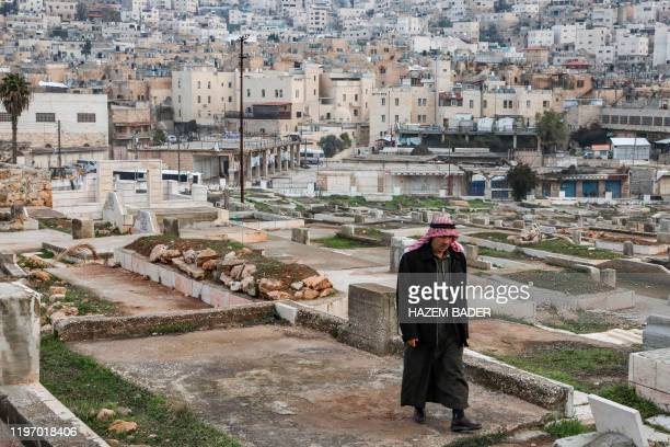 TOPSHOT An elderly Palestinian walks through a cemetery in the flashpoint city of Hebron in the occupied West Bank on January 28 with the background...