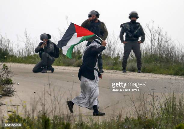 An elderly Palestinian walks waving a Palestinian flag as Israeli security forces stand behind one of them kneeling and taking aim during a...