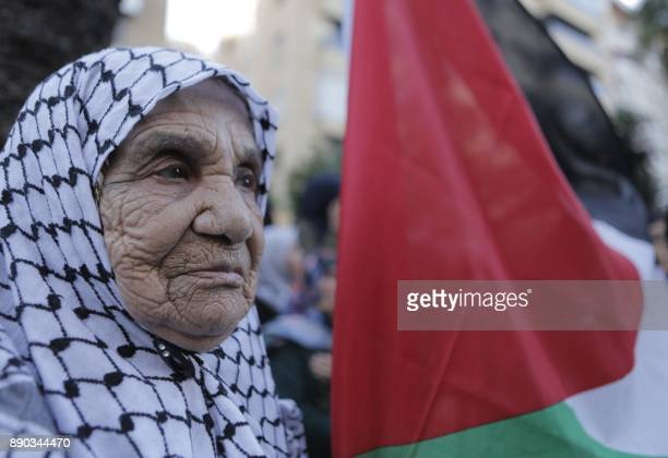 An elderly Palestinian woman holding a national flag joins supporters of Lebanon's Hezbollah Shiite movement in a rally held in the Lebanese capital...
