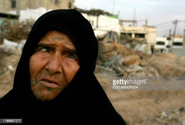 An elderly Palestinian woman inspects the site of a demolished house in northern Gaza Strip town of Beit Lahia 14 October 2004. Five more...