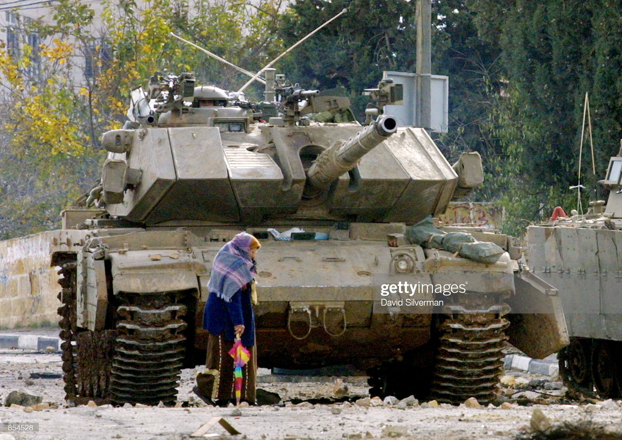 https://media.gettyimages.com/photos/an-elderly-palestinian-woman-makes-her-way-home-past-an-israeli-tank-picture-id854528?s=2048x2048