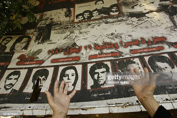 An elderly Palestinian woman prays in front of a poster bearing pictures of her killed relatives during a memorial ceremony commemorating the 28th...