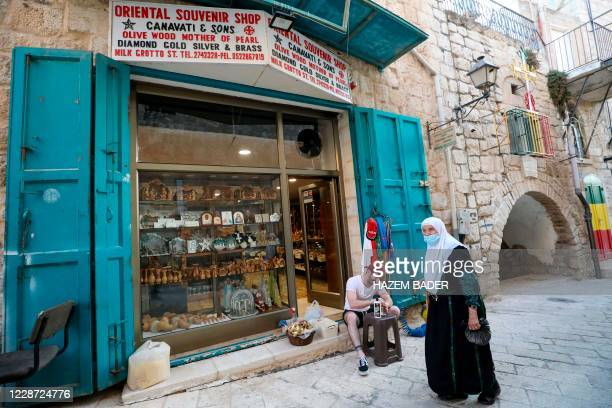 An elderly Palestinian woman walk by as a man cleans souvenirs at one of the Canavati family souvenir shops, currently closed amid lockdown due to...