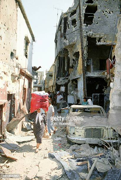 An elderly Palestinian woman walks in the ruins of Sabra Palestinian refugee camp 27 May 1985 in the southern West Beirut. Fighting between...
