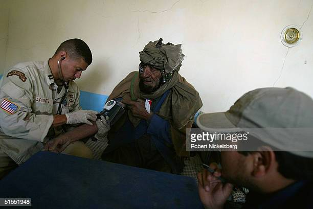 An elderly Pashtun man sits in a medical clinic in Wazakhwa as he has his blood pressure checked by a US Army medic from the 25th Infantry Division...