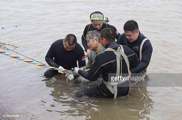 An elderly passenger is escorted to the river bank after being rescued from the Dongfangzhixing or Eastern Star vessel which sank in the Yangtze...