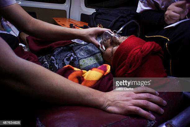 An elderly patient takes oxygen from a volunteer paramedic December 11 2013 in Guatemala City Guatemala The bomberos voluntarios are a volunteer fire...