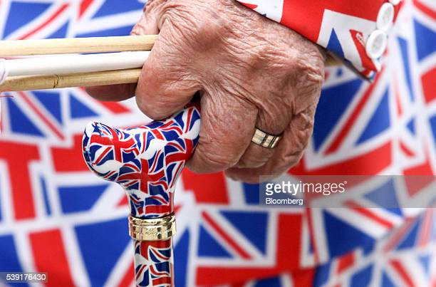An elderly pedestrian holds a walking stick featuring a pattern of a British Union flag commonly known as a Union Jack in London UK on Friday June 10...