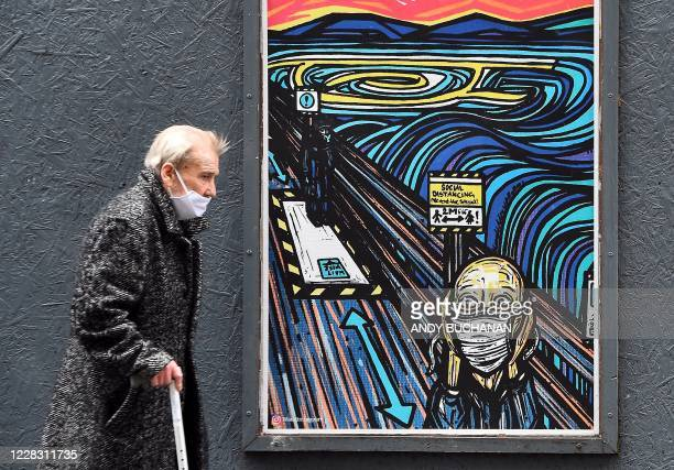 TOPSHOT An elderly pedestrian wearing a face mask or covering due to the COVID19 pandemic walks past graffiti depicting the subjects within famous...