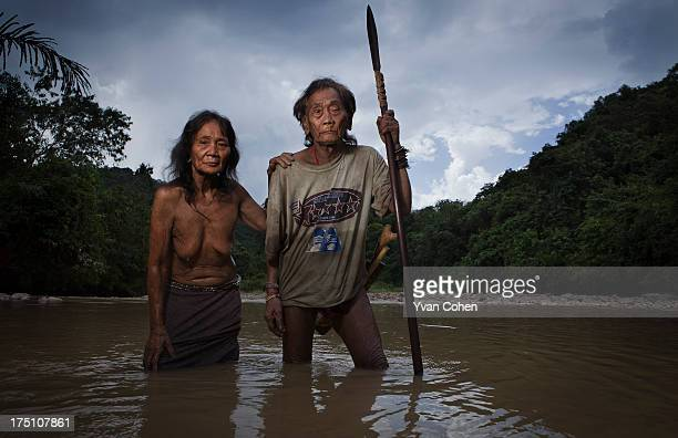 An elderly Penan couple stand for a symbolic portrait in the river near their longhouse in an area known as Long Napir A new dam project threatens to...