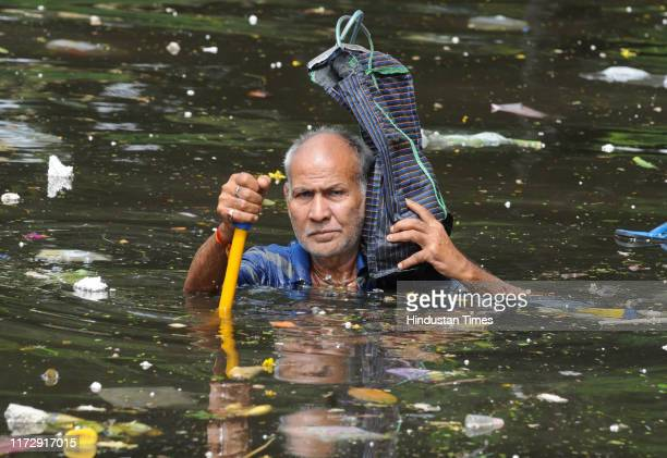 An elderly person leaves his residence and enters the filth ridden waters in the waterlogged area of Rajender Nagar on October 1 2019 in Patna India...