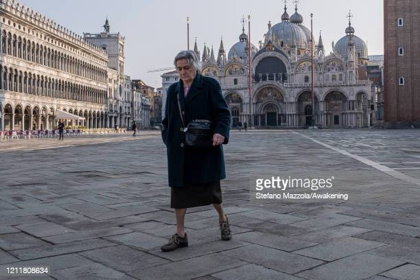 An elderly person walks dejected into Piazza San Marco on March 11 2020 A local walks near the Grand Canal with a protective face mask in Venice...