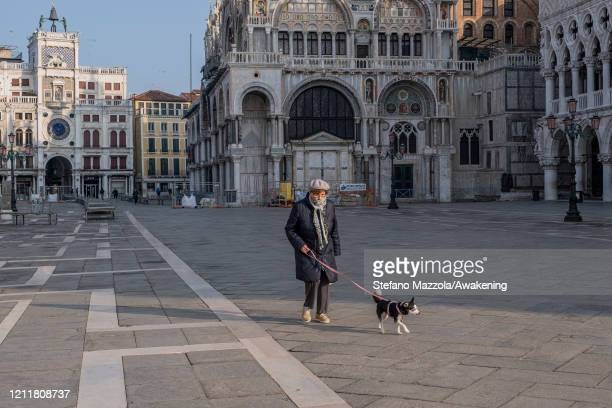 An elderly person walks in an empty Piazza San Marco with his dog on March 11 2020 A local walks near the Grand Canal with a protective face mask in...