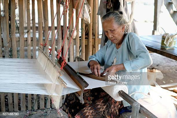 An elderly Phu Tai ethnic minority woman weaves handspun cotton Ban Lahanam Savannakhet province Lao PDR Cotton has been grown in Laos for centuries...