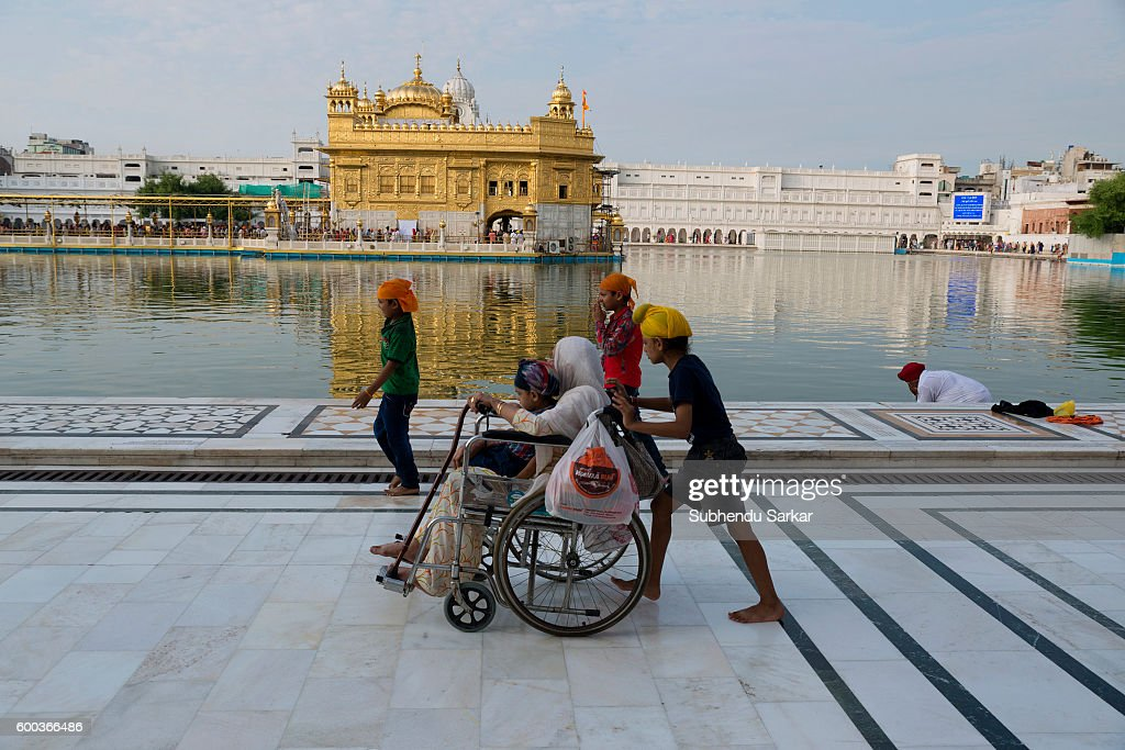 An elderly pilgrim is being carried on wheelchair in the Golden Temple complex Sri Harmandir Sahib or Sri Darbar Sahib or the `Golden Temple` is the..