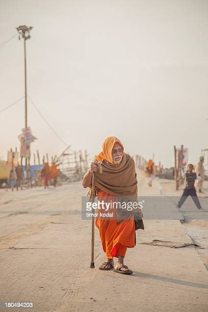 An elderly pilgrim moves along one of the main roads of the Kumbh Mela 2013 festival site with his walking stick in the afternoon.