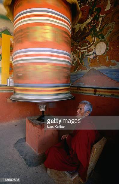 an elderly pilgrim turns a prayer wheel in punakha dzong. - プナカ ストックフォトと画像