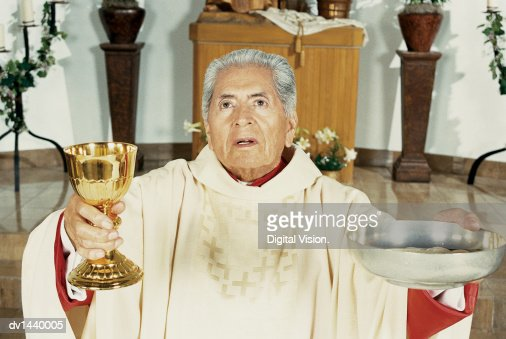 An Elderly Priest Blesses Communion Wine In A Golden Cup And
