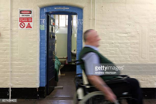 An elderly prisoner goes past his cell in a wheelchair in the vulnerable prisoners unit which is located on the H wing of the Onslow building at...
