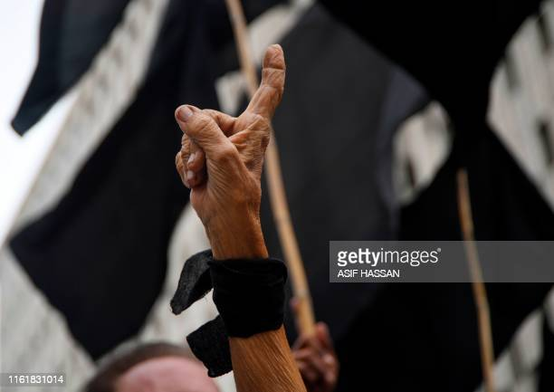 An elderly protester wears a black ribbon on her wrist as she takes part in a protest in Karachi on August 15 as the country observes 'Black Day' on...
