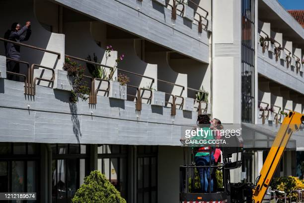 An elderly resident at Santo Antonio retirement house in Figueira da Foz, talks with their relatives who stand on a manlift crane to keep their...