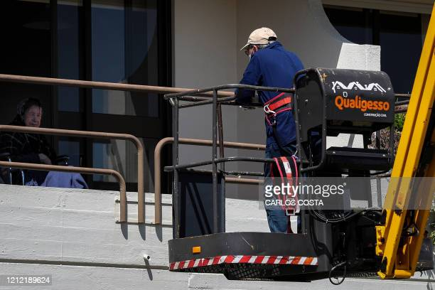 An elderly resident at Santo Antonio retirement house in Figueira da Foz, talks with her relative, who stands on a manlift crane to keep their social...
