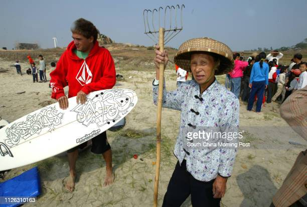An elderly resident checks out the action with Christian surfer from Australia with 'Jesus Saves' written on his board during the 720 surfing...