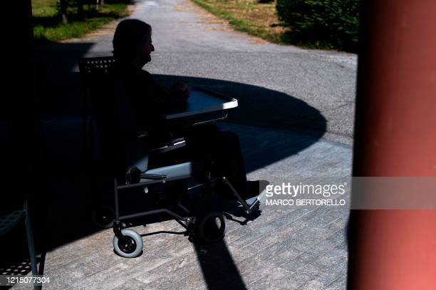 An elderly resident in a wheelchair waits for the visit of relatives at the Tapparelli retirement home on May 25 2020 in Saluzzo near Cuneo Piedmont...